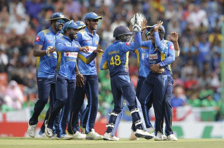 Sri Lankan team members celebrate the dismissal of England's Jason Roy with their bowler Akila Dananjaya, right, during their fourth one-day international cricket match in Pallekele, Sri Lanka, Saturday, Oct. 20, 2018. (AP Photo/Eranga Jayawardena)