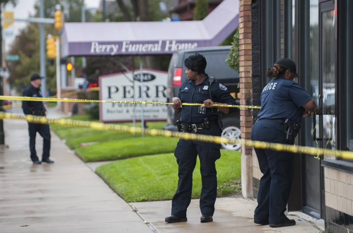 Detroit Police officers use crime scene tape to cordon off the area while they execute a search warrant at the Perry Funeral Home in Detroit on Friday, Oct. 19, 2018. Police removed the remains of 63 fetuses from the funeral home and regulators shuttered the business amid a widening investigation of alleged improprieties at local funeral homes. (John T. Greilick/Detroit News via AP)
