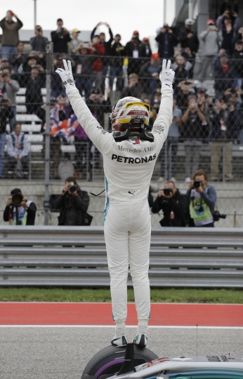 Mercedes driver Lewis Hamilton, of Britain, waves to fans after winning the pole for the Formula One U.S. Grand Prix auto race at the Circuit of the Americas, Saturday, Oct. 20, 2018, in Austin, Texas. (AP Photo/Darron Cummings)