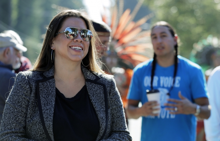 "In this Oct. 17, 2018 photo, Nicole Willis, left, a member of the Confederated Tribes of the Umatilla Reservation who lives in Seattle, listens to speakers at a rally in Lacey, Wash. Willis grew up hours away from the Confederated Tribes of the Umatilla Reservation in the Pacific Northwest, which she calls home. She traveled often from Seattle for cultural events and to spend summers with her grandmother. To her, being Native American means her family is part of a distinct, interconnected community that has existed since ancient times. Her tribe requires citizens to be one-quarter Native American, with 1/16 specific to the tribe, but she said ""theoretically, it shouldn't matter."" (AP Photo/Ted S. Warren)"