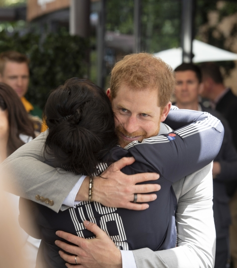 Britain's Prince Harry hugs a guest during a lunchtime reception hosted by Australian Prime Minister Scott Morrison with Invictus Games competitors, their families and friends in Sydney Sunday, Oct. 21, 2018. (Paul Edwards/Pool Photo via AP)