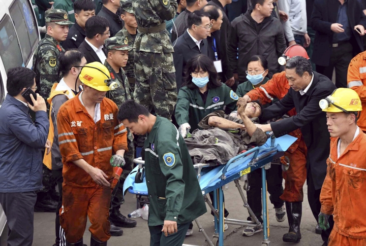 In this photo released by China's Xinhua News Agency, a worker is carried on a stretcher out of the Longyun coal mine in Yuncheng County, east China's Shandong Province, Sunday, Oct. 21, 2018. Twenty were trapped in the coal mine Sunday after a rock burst destroyed part of a mining tunnel. (Guo Xulei/Xinhua via AP)