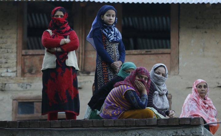 Kashmiri women and girls watch the funeral procession of a civilian Uzair Mushtaq in Kulgam 75 Kilometers south of Srinagar, Indian controlled Kashmir, Sunday, Oct. 21, 2018. Three local rebels were killed in a gunbattle with Indian government forces in disputed Kashmir on Sunday, and six civilians were killed in an explosion at the site after the fighting was over, officials and residents said. (AP Photo/Mukhtar Khan)
