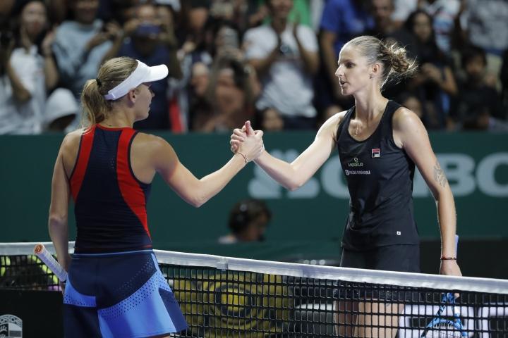 Caroline Wozniacki of Denmark, left, greets Karolina Pliskova of the Czech Republicafter their match at the WTA tennis finals in Singapore, Sunday, Oct. 21, 2018. (AP Photo/Vincent Thian)