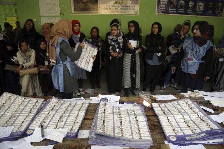Afghan election workers count ballots during the parliamentary elections at a polling station in Kabul, Afghanistan, Sunday, Oct. 21, 2018. Te elections entered a second day after delays caused by violence and technical issues, as a roadside bomb killed nearly a dozen civilians on Sunday, including several children. (AP Photo/Rahmat Gul)