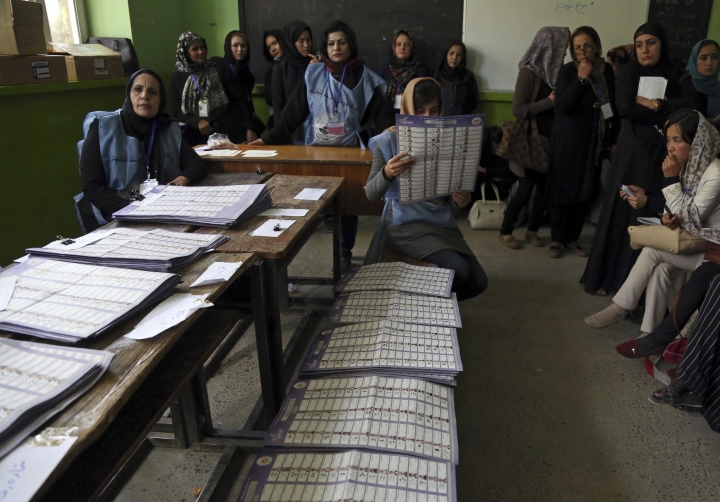 An Afghan election worker counts ballots while monitors observe the process, during parliamentary elections, at a polling station in Kabul, Afghanistan, Sunday, Oct. 21, 2018. The elections entered a second day after delays caused by violence and technical issues, as a roadside bomb killed nearly a dozen civilians on Sunday, including several children. (AP Photo/Rahmat Gul)