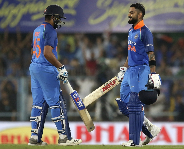 India's Rohit Sharma, left, walks to congratulate captain Virat Kohli on scoring a century during the first one-day international cricket match between India and West Indies in Gauhati, India, Sunday, Oct. 21, 2018. (AP Photo/Anupam Nath)