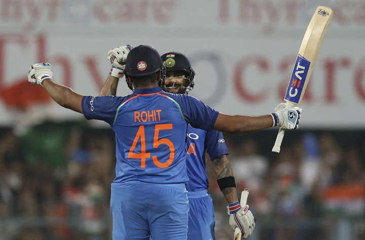 India's Rohit Sharma, back to camera, celebrates with captain Virat Kohli after scoring a century during the first one-day international cricket match between India and West Indies in Gauhati, India, Sunday, Oct. 21, 2018. (AP Photo/Anupam Nath)