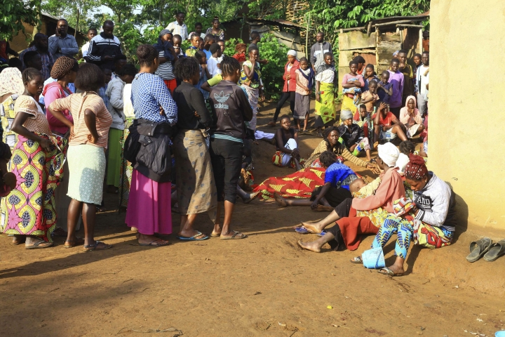 In this photo taken Friday, Oct 5, 2018, family members and onlookers mourn over the bodies of civilians killed by The Allied Democratic Forces rebels in Beni, Eastern Congo. Congo' military said Sunday Oct. 21, 2018, that rebels attacked an Ebola treatment centre in Beni, leaving over a dozen civilians dead and abducted about a dozen children, which could force crucial virus containment efforts to be suspended in the area. (AP Photo/Al-hadji Kudra Maliro)