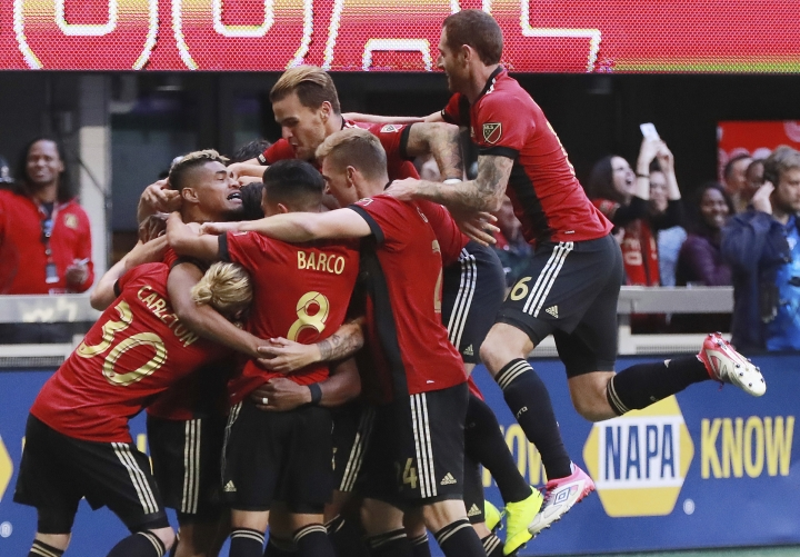Atlanta United players mob Franco Escobar after his goal for a 1-0 lead over the Chicago Fire during the first half in a MLS soccer match on Sunday, Oct 21, 2018, in Atlanta. (Curtis Compton/Atlanta Journal-Constitution via AP)