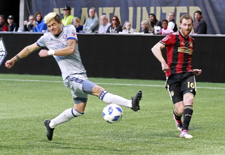 Atlanta United's Chris McCann, left, scores a goal past Chicago Fire midfielder Diego Campos during the first half of an MLS soccer match on Sunday, Oct. 21, 2018, in Atlanta. (Curtis Compton/Atlanta Journal-Constitution via AP)