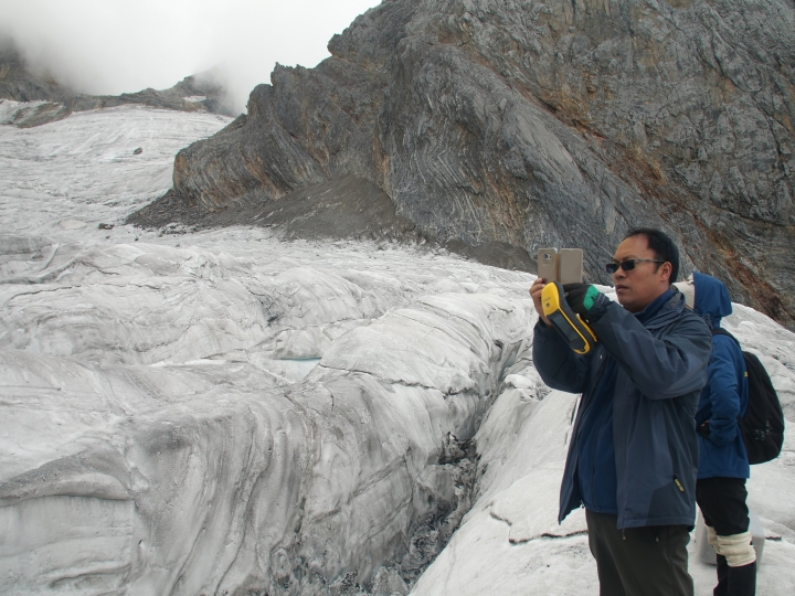 This Sept. 22, 2018 photo shows glaciologist Wang Shijin photographing the Baishui Glacier No.1 on the Jade Dragon Snow Mountain in the southern province of Yunnan in China. Scientists say the glacier is one of the fastest melting glaciers in the world due to climate change and its relative proximity to the Equator. It has lost 60 percent of its mass and shrunk 250 meters since 1982. (AP Photo/Sam McNeil)
