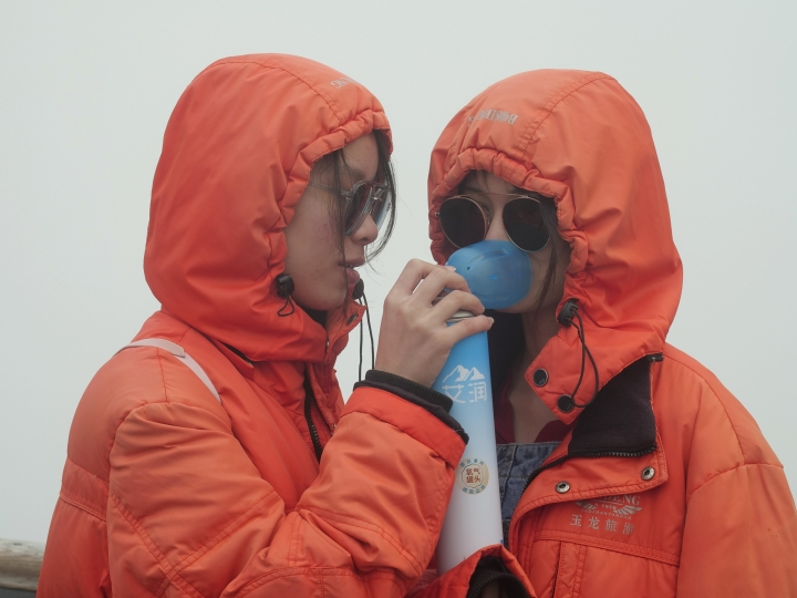 This Sept. 22, 2018 photo shows tourists sharing an oxygen tank 4,680 meters above sea level atop atop of the Jade Dragon Snow Mountain in the southern province of Yunnan in China overlooking a glacier scientists say is one of the fastest melting glaciers in the world due to climate change and its relative proximity to the Equator. (AP Photo/Sam McNeil)