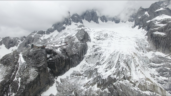 In this photo taken May 2018 and released by Yulong Snow Mountain Glacier and Environmental Observation Research Station on Oct. 18, 2018, the Baishui Glacier No.1 is visible next to a tourist viewing platform high in the Jade Dragon Snow Mountain in the southern province of Yunnan in China. Scientists say the glacier is one of the fastest melting glaciers in the world due to climate change and its relative proximity to the Equator. It has lost 60 percent of its mass and shrunk 250 meters since 1982. (Yulong Snow Mountain Glacier and Environmental Observation Research Station via AP)