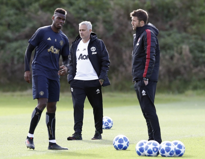 Manchester United manager Jose Mourinho, centre and player Paul Pobga, left and assistant coach Michael Carrick attend a training session at the Aon Training Complex, in Manchester, England, Monday, Oct. 22, 2018. Manchester United will play Juventus in a group stage Group H Champions League soccer match on Tuesday. (Martin Rickett/PA via AP)