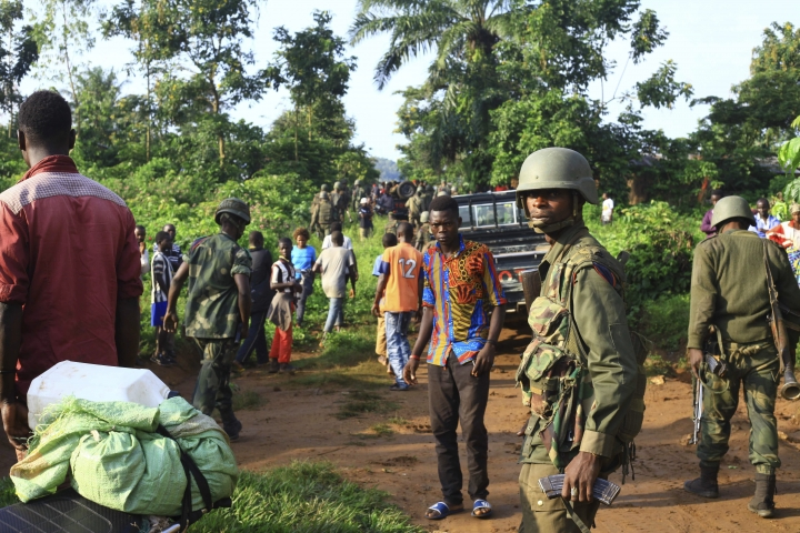 In this photo taken Friday, Oct 5, 2018, Congolese Soldiers patrol in an area civilians were killed by The Allied Democratic Forces rebels in Beni, Eastern Congo. Congo' military said Sunday Oct. 21, 2018, that rebels attacked an Ebola treatment centre in Beni, leaving over a dozen civilians dead and abducted about a dozen children, which could force crucial virus containment efforts to be suspended in the area. (AP Photo/Al-hadji Kudra Maliro)