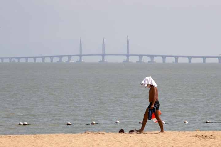 A man walks past a beach as the Zhuhai-Macau-Hong Kong Bridge are seen at the back in Zhuhai in south China's Guangdong province, Monday, Oct. 22, 2018. The bridge, the world's longest cross-sea project, which has a total length of 55 kilometers (34 miles), will have opening ceremony in Zhuhai on Oct. 23. (AP Photo/Andy Wong)