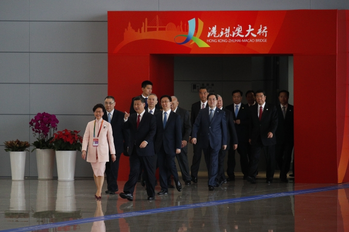 Chinese President Xi Jinping, front right, chats with Hong Kong Chief Executive Carrie Lam, front left, as they arrive for the opening ceremony for the China-Zhuhai-Macau-Hong Kong Bridge in Zhuhai in south China's Guangdong province, Tuesday, Oct. 23, 2018. The bridge, the world's longest cross-sea project, which has a total length of 55 kilometers (34 miles), will have opening ceremony in Zhuhai on Tuesday. (AP Photo/Andy Wong)