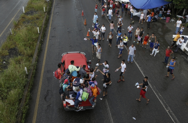 Mexicans from religious organizations hand out small bags containing water, toilet paper, diapers and medicine to Central American migrants who got a free ride from a motorist, in Xochiltepec, Mexico, Monday, Oct. 22, 2018. Motorists in pickups and other vehicles have been offering the Central American migrants rides, often in overloaded truck beds, as the group of about 7,000 people heads to the U.S. border. (AP Photo/Moises Castillo)