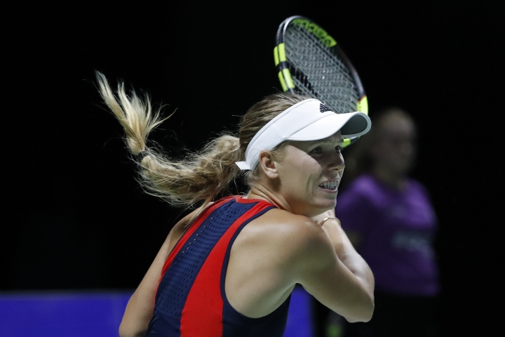 Caroline Wozniacki of Denmark plays a return shot while competing against Petra Kvitova of the Czech Republic during their women's singles match at the WTA tennis finals in Singapore, Tuesday, Oct. 23, 2018. (AP Photo/Vincent Thian)