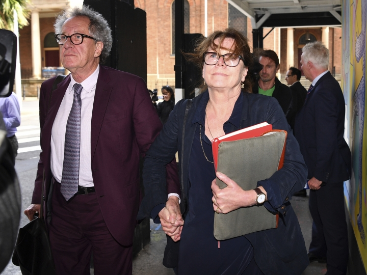 Australian actor Geoffrey Rush, left, and his wife Jane Menelaus leave the Federal Court in Sydney, Wednesday, Oct. 24, 2018. Rush is suing Nationwide News for defamation. Rush's wife has wept while telling a court how her husband cried and curled up in the fetal position after a newspaper alleged he'd behaved inappropriately toward a co-star. (Brendan Esposito/AAP Image via AP)
