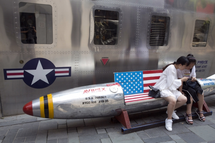 FILE - In this July 6, 2018, file photo, Chinese women look at phone near a rocket shaped bench with an American flag used as a marketing gimmick for a U.S. apparel shop in Beijing. The U.S. will not send a high-ranking official to attend a major investment fair in China next month, the U.S. Embassy said Wednesday, Oct. 24, 2018, in a move underscoring worsening trade frictions between the world's two largest economies. (AP Photo/Ng Han Guan, File)