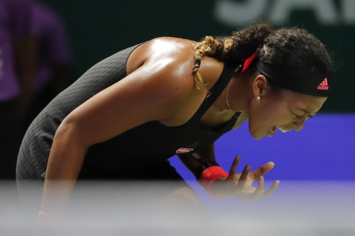 Naomi Osaka of Japan reacts while playing against Angelique Kerber of Germany during their women's singles match at the WTA tennis finals in Singapore, Wednesday, Oct. 24, 2018. (AP Photo/Vincent Thian)