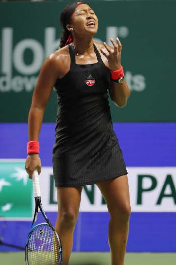 Naomi Osaka of Japan reacts after losing a point while playing against Angelique Kerber of Germany during their women's singles match at the WTA tennis finals in Singapore, Wednesday, Oct. 24, 2018. (AP Photo/Vincent Thian)