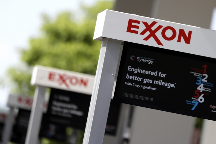 FILE- This April 25, 2017, file photo, shows Exxon service station signs in Nashville, Tenn. New York's attorney general is suing Exxon Mobil saying the company misled investors about the risks climate change posed to its business. (AP Photo/Mark Humphrey, File)