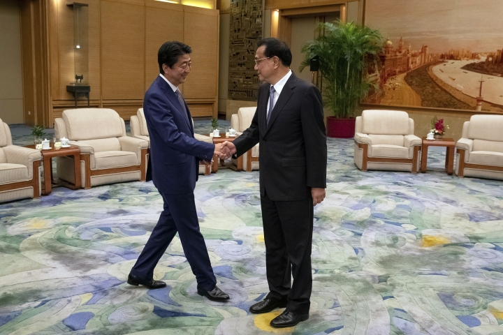 Chinese Premier Li Keqiang, right, and Japanese Prime Minister Shinzo Abe shake hands during their meeting at the Great Hall of the People in Beijing, Thursday, Oct. 25, 2018. Abe arrived in Beijing on Thursday as both countries try to repair ties that have been riven by disputes over territory, military expansion in the Pacific and World War II history. (Roman Pilipey/Pool Photo via AP)