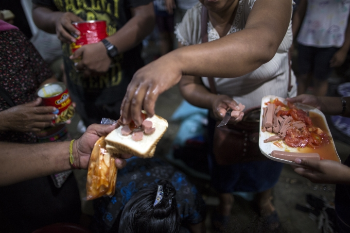 Central American migrants traveling with a caravan to the U.S. receive donated food outside the Catholic Church in Mapastepec, Mexico, Wednesday, Oct. 24, 2018. Thousands of Central American migrants renewed their hoped-for march to the United States on Wednesday, setting out before dawn with plans to travel another 45 miles (75 kilometers) of the more than 1,000 miles that still lie before them. (AP Photo/Rodrigo Abd)