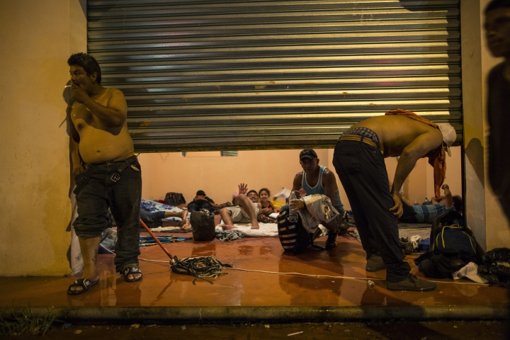 Central American migrants rests inside a commercial space, after a heavy rain in Mapastepec, Mexico, Wednesday, Oct. 24, 2018. Thousands of Central American migrants renewed their hoped-for march to the United States on Wednesday, setting out before dawn with more than 1,000 miles still before them. (AP Photo/Rodrigo Abd)