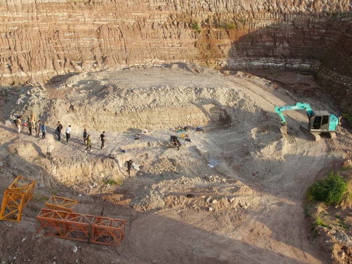 In this Sept. 13, 2018, photo, workers excavate a dinosaur dig site in Yanji, China. The excavation, led by paleontologist Xu Xin, begun after construction crews erecting new apartment buildings accidentally uncovered dinosaur bones and other fossils, dating back 100 million years. (AP Photo/Sam McNeil)
