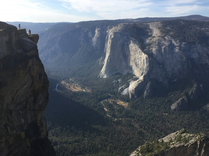 FILE - In this Sept. 27, 2018 file photo a wedding couple are seen being photographed at Taft Point in California's Yosemite National Park. A Yosemite National Park official says two visitors have died in a fall from the popular overlook. Park rangers are trying to recover the bodies of a man and a woman Thursday, Oct.25, 2018. He didn't say when the couple fell from Taft Point, which is at an elevation of 7,500 feet. Gediman says the deaths are being investigated and offered no other information. (AP Photo/Amanda Lee Myers,File)
