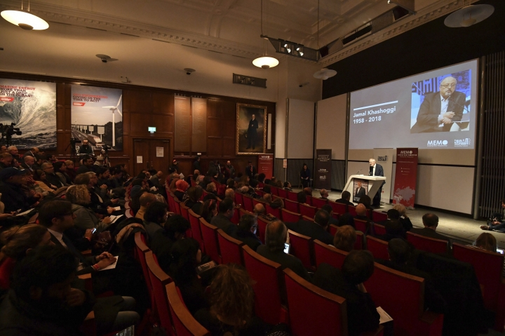 People attend a memorial event for killed Saudi journalist Jamal Khashoggi, seen on screen, at the Mechanical Engineers Institute in London, Monday Oct. 29, 2018. The Al Sharq Forum think tank and Middle East Monitor have organised the event in honour of the murdered journalist Khashoggi who died in the Saudi consulate in Turkey. (John Stillwell/PA via AP)
