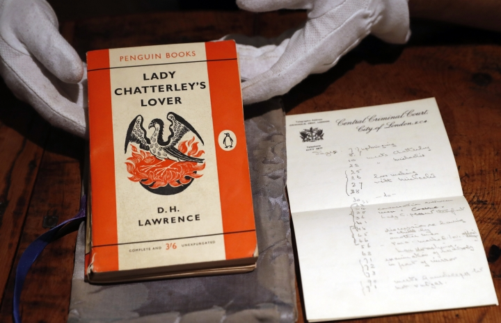 """FILE - In this Friday, Oct. 26, 2018 file photo, a copy of D.H Lawrence's book """"Lady Chatterley's Lover"""" that was the judge's personal version used in the infamous 1960 Chatterley trial, on view in Sotheby's auction house in London. The copy used by the judge in the U.K. obscenity trial of the novel's publisher has sold at auction for 56,250 pounds ($72,000), more than three times its pre-sale estimate. The tattered Penguin paperback, along with a damask bag designed to stop photographers snapping the judge with the scandalous tome, sold to an anonymous bidder at Sotheby's in London on Tuesday Oct. 31, 2018. (AP Photo/Alastair Grant, File)"""