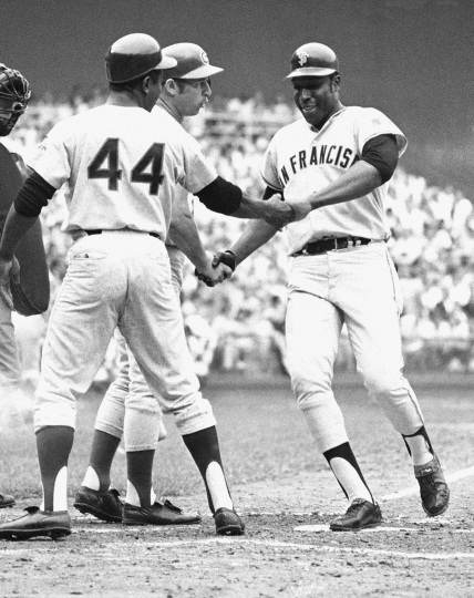 """FILE - In this July 23, 1969, file photo, National League's Willie McCovey of San Francisco is congratulated on crossing home in the third inning of the baseball All-Star Game in Washington after hitting in Hank Aaron (44) in Washington. McCovey hit another home in the next inning. Also shaking his hand is Ron Santo, on deck. McCovey, the sweet-swinging Hall of Famer nicknamed """"Stretch"""" for his 6-foot-4 height and those long arms, has died. He was 80. The San Francisco Giants announced his death, saying the fearsome hitter passed """"peacefully"""" Wednesday afternoon, Oct. 31, 2018, """"after losing his battle with ongoing health issues."""" (AP Photo, File)"""