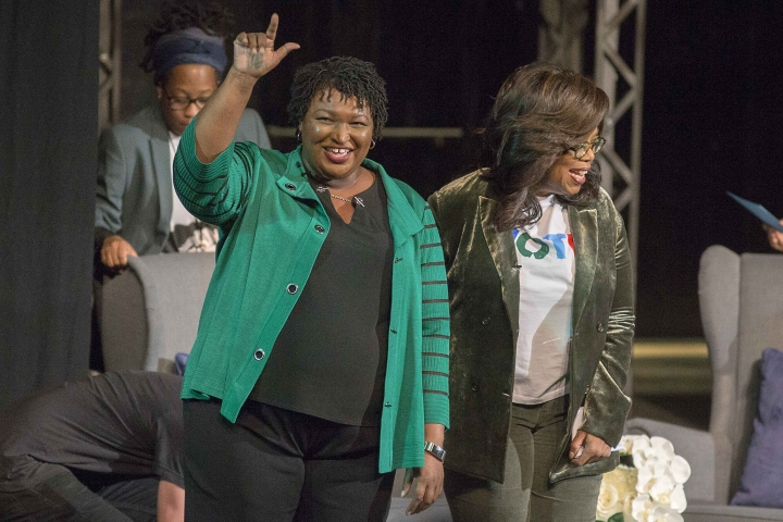 Oprah Winfrey and Georgia gubernatorial candidate Stacey Abrams greet a crowd gathered for a town hall conversation at the Cobb Civic Center's Jennie T. Anderson Theatre in Marietta, Ga., Thursday, Nov. 1, 2018. Winfrey visited Georgia on Thursday to canvass neighborhoods in Metro Atlanta and show her support for gubernatorial candidate Stacey Abrams. (Alyssa Pointer /Atlanta Journal-Constitution via AP)