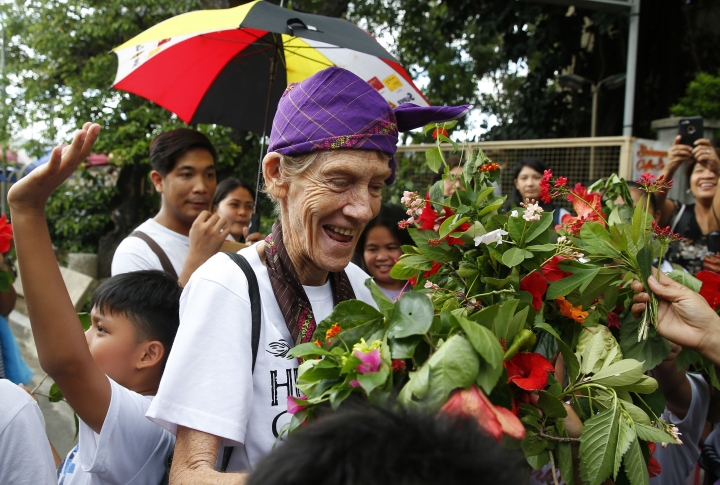 Australian Roman Catholic nun Sister Patricia Fox receives flowers from children of informal settlers as she arrives for a visit to the Redemptorist Church prior to her departure for Australia Saturday, Nov. 3, 2018 in suburban Paranaque city, south of Manila, Philippines. Sister Fox decided to leave after 27 years in the country after the Immigration Bureau denied her application for the extension of her visa. The Philippine immigration bureau has ordered the deportation of Fox who has angered the president by joining anti-government rallies. (AP Photo/Bullit Marquez)