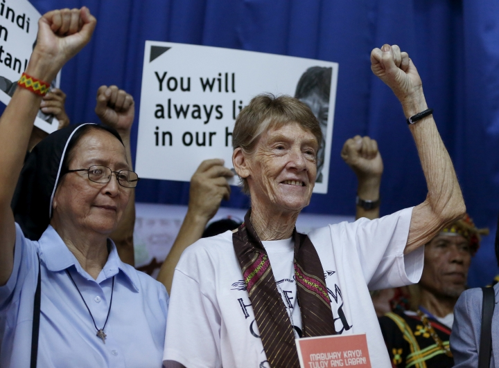 Australian Roman Catholic nun Sister Patricia Fox, right, clenches her fist following a news conference hours before her departure for Australia Saturday, Nov. 3, 2018, in Manila, Philippines. Sister Fox decided to leave after 27 years in the country after the Immigration Bureau denied her application for the extension of her visa. The Philippine immigration bureau has ordered the deportation of Fox who has angered the president by joining anti-government rallies. (AP Photo/Bullit Marquez)