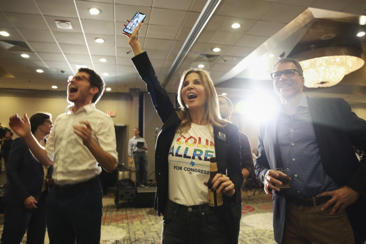 David Rosen, from left, Jennifer Karol and her husband Tom Karol react to an update on the 32nd Texas congressional race during an election night party for Democratic candidate Colin Allred at the Magnolia Hotel Dallas Park Cities in Dallas, Tuesday, Nov. 6, 2018. Allred is running against incumbent Republican Pete Sessions for the Texas 32nd U.S. congressional house district. (AP Photo/Andy Jacobsohn)