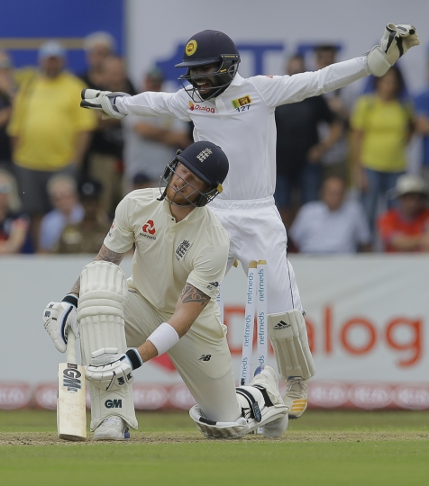 England's Ben Stokes reacts after being bowled out as Sri Lankan wicketkeeper Niroshan Dickwella celebrates during the first day of the first test cricket match between Sri Lanka and England, in Galle, Sri Lanka, Tuesday, Nov. 6, 2018. (AP Photo/Eranga Jayawardena)