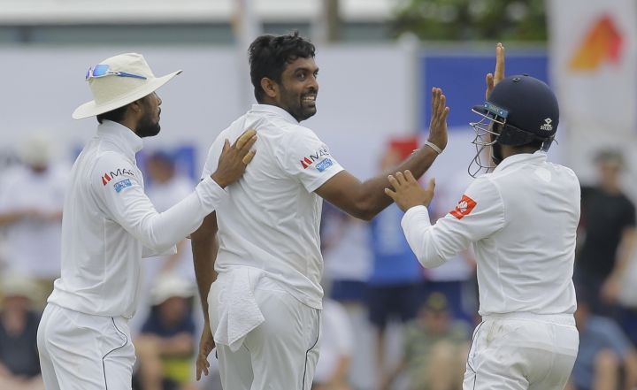 Sri Lanka's Dilruwan Perera, center, celebrates the dismissal of England's Jos Buttler during the first day of the first test cricket match between Sri Lanka and England, in Galle, Sri Lanka, Tuesday, Nov. 6, 2018. (AP Photo/Eranga Jayawardena)