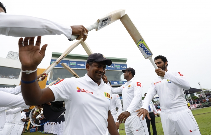 Sri Lanka's spin bowler Rangana Herath waves as he is greeted with an arch of bats while he enters the field for the last match of his test cricket career, the first test cricket match between Sri Lanka and England, in Galle, Sri Lanka, Tuesday, Nov. 6, 2018. (AP Photo/Eranga Jayawardena)