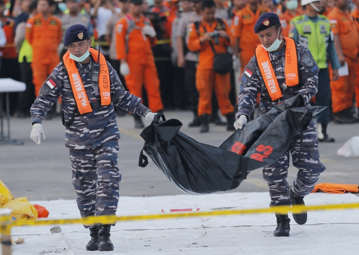 """FILE - In this Thursday, Nov. 1, 2018, file photo, navy personnel carry the remains of a victim of Lion Air jet that crashed into the sea at the Tanjung Priok Port in Jakarta, Indonesia. Boeing Co. says it has issued a safety bulletin that reiterates guidelines on how pilots should respond to erroneous data from an """"angle of attack"""" sensor following last week's crash of a Boeing plane in Indonesia that killed 189 people. (AP Photo/Tatan Syuflana, File)"""
