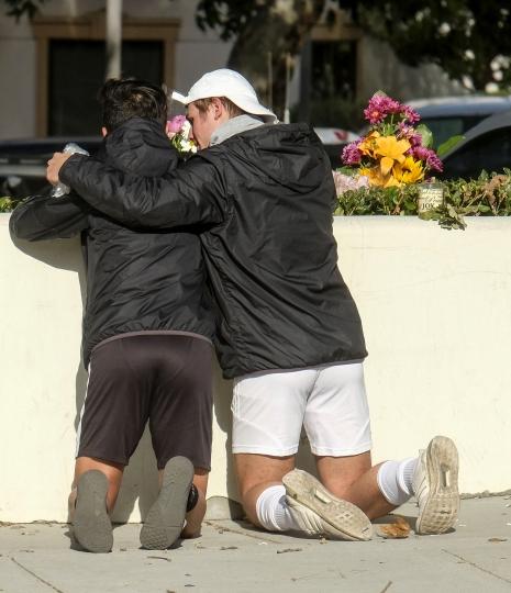 People place flowers near the scene of a mass shooting Thursday, Nov. 8, 2018, in Thousand Oaks, Calif., after a gunman opened fire Wednesday evening inside a country music bar, killing multiple people including a responding sheriff's sergeant. (AP Photo/Ringo H.W. Chiu)