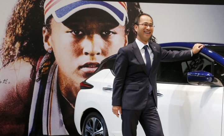 "In this Nov. 1, 2018, photo, Masao Tsutsumi, general manager in charge of Osaka-related marketing at Nissan Motor Co., stands with a Leaf electric vehicle in front of a giant poster of Japanese tennis player Naomi Osaka at the company's showroom in Yokohama, south of Tokyo. Osaka is headed for big money with both Japanese and global appeal. Nissan signed Osaka as its three-year ""brand ambassador"" in September. Although the deal was in the works for a while, the timing couldn't have been better, coming right after the U.S. Open where she beat Serena Williams of the U.S. (AP Photo/Yuri Kageyama)"