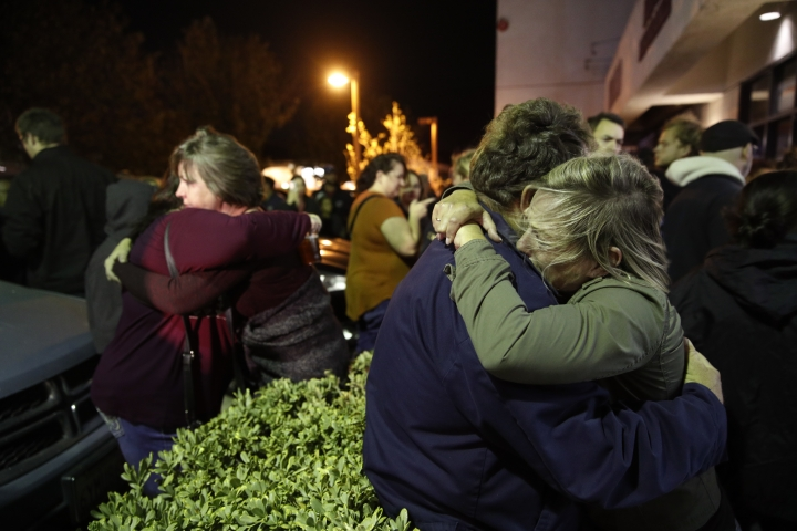Eva Mills, right, and Holden Grzywacz, two survivors of the Las Vegas mass shooting, mourn the death of Sean Adler during a vigil at the Rivalry Roasters coffee shop Thursday, Nov. 8, 2018, in Simi Valley, Calif. Adler was killed in Wednesday night's shooting at the Borderline Bar and Grill in Thousand Oaks, Calif. (AP Photo/Jae C. Hong)