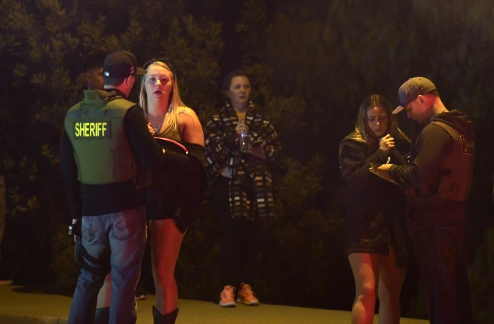 "Sheriff's deputies speak to potential witnesses as they stand near the scene of a mass shooting Thursday, Nov. 8, 2018, in Thousand Oaks, Calif., where a gunman opened fire Wednesday night inside a country dance bar crowded with hundreds of people on ""college night,"" killing at least 12 people, including a sherif's deputy who rushed to the scene. Ventura County sheriff's spokesman says the gunman is dead inside the bar. (AP Photo/Mark J. Terrill)"