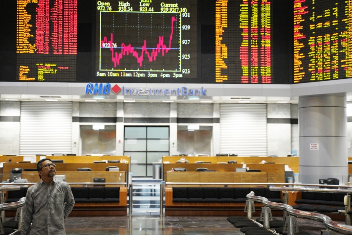 An investor walks in front of private stock trading boards at a private stock market gallery in Kuala Lumpur, Malaysia, Friday, Nov. 9, 2018. Asian stock markets fell Friday after a post-election Wall Street rally faded amid expectations of U.S. interest rate hikes despite the Federal Reserve's decision to hold off this week. (AP Photo/Yam G-Jun)